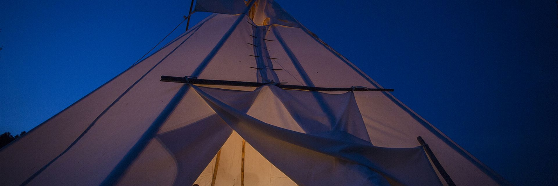 A view of the inside of a Teepee from the opening, revealing people inside.
