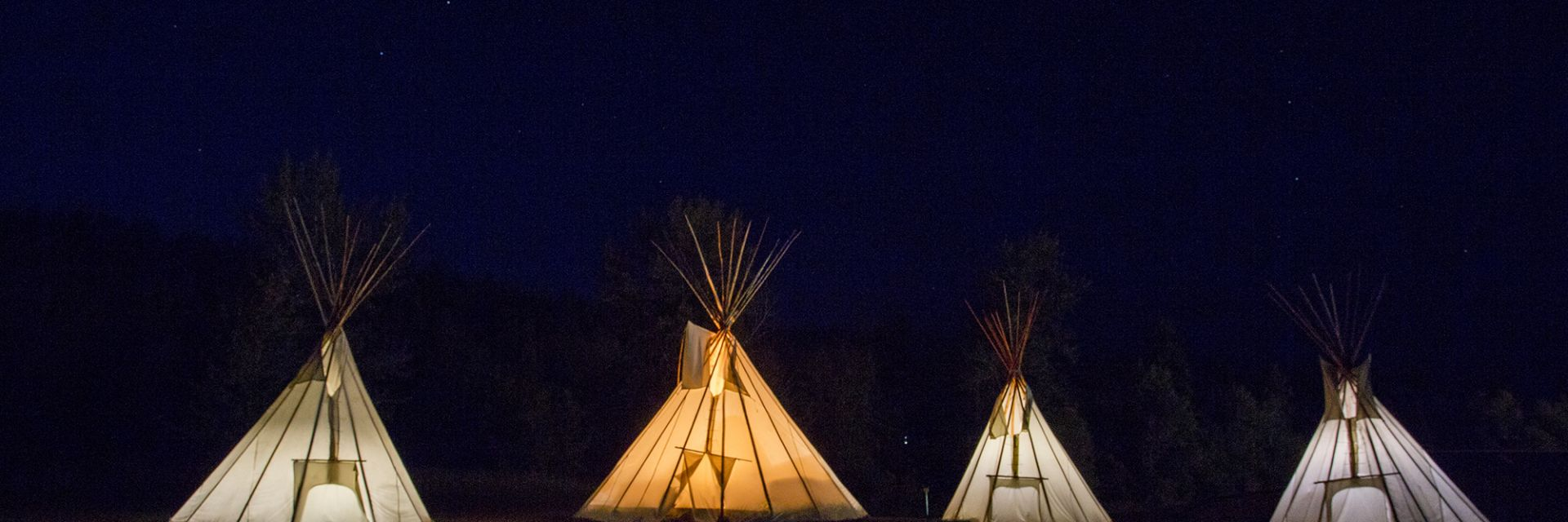A nighttime view of four teepees