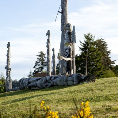A totem pole stands in a grassy field with yellow flowers in the foreground