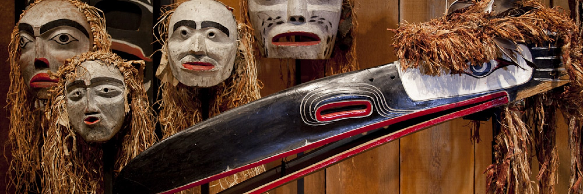 A collection of Indigenous masks hung on a wooden wall