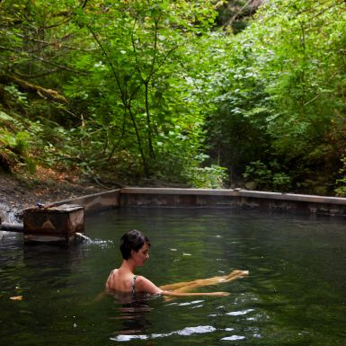 A woman stretches her legs at the Hldu Isgwit Hot Springs