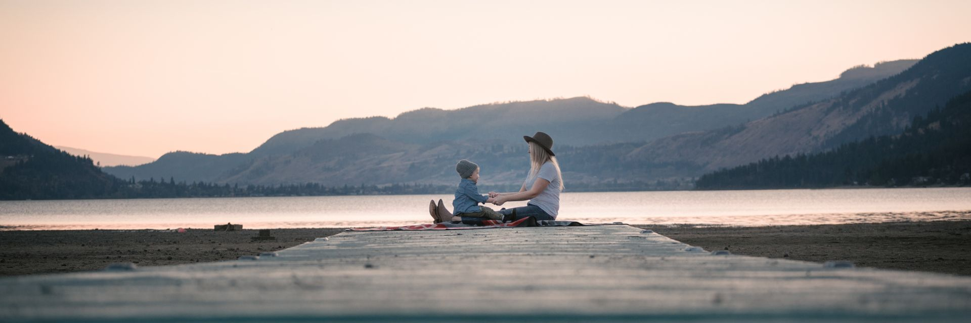 A mother and child sit at the end of a boardwalk and hold hands next to the shore