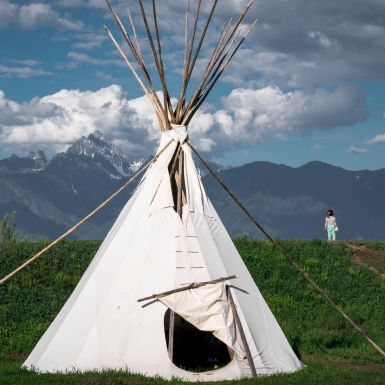 A white teepee stands in the foreground with the Kootenay Rockies in the background