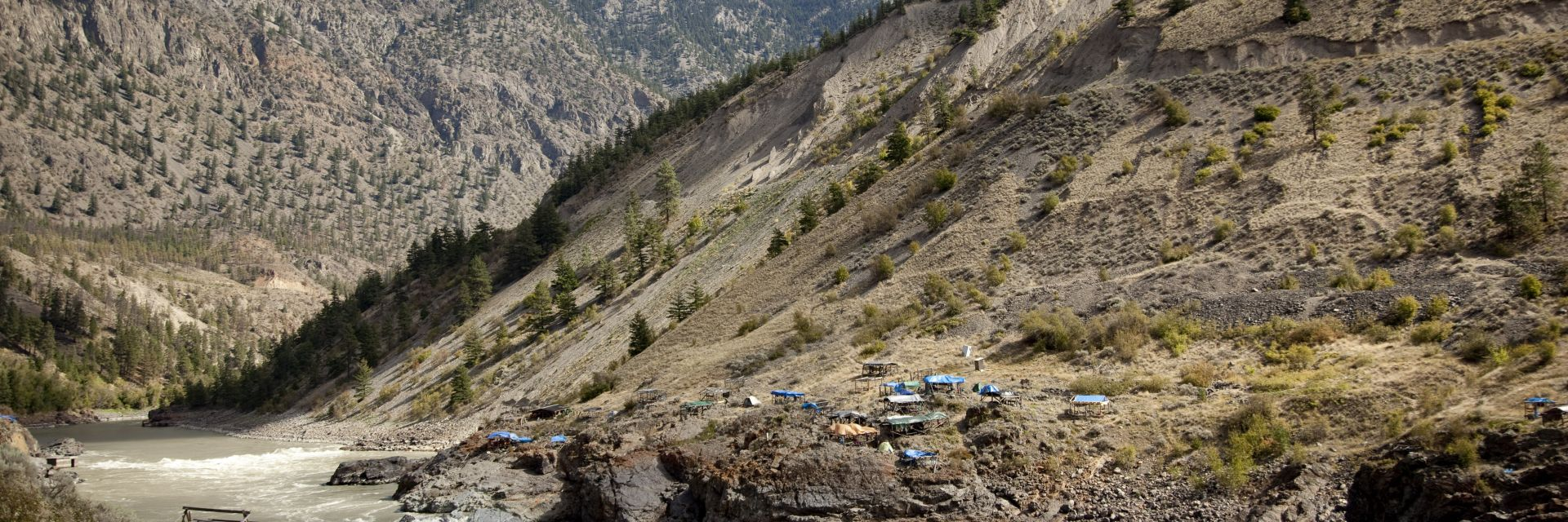 Tents are pitched on both sides of a river at the bottom of hill in Lillooet, BC.