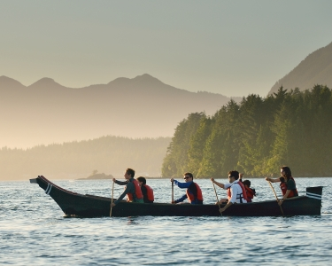 People paddling together in a canoe on a body of water
