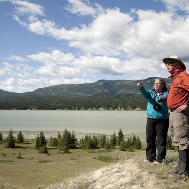 A woman and man stand together on a sandy hilltop next to a lake