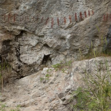 A rock wall with red and black markings