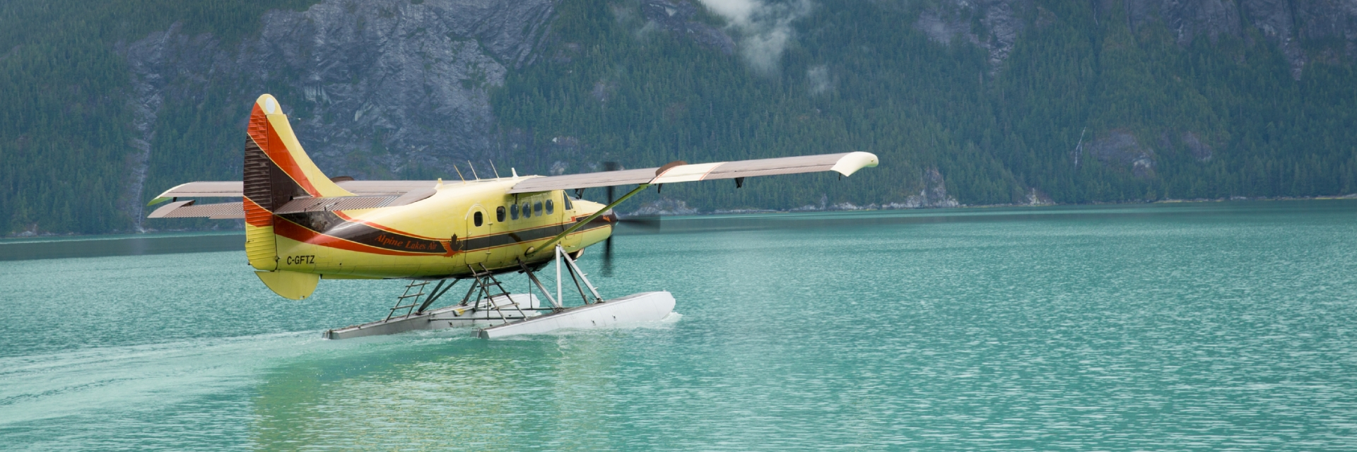 A yellow and red sea plane sitting in a bright blue lake