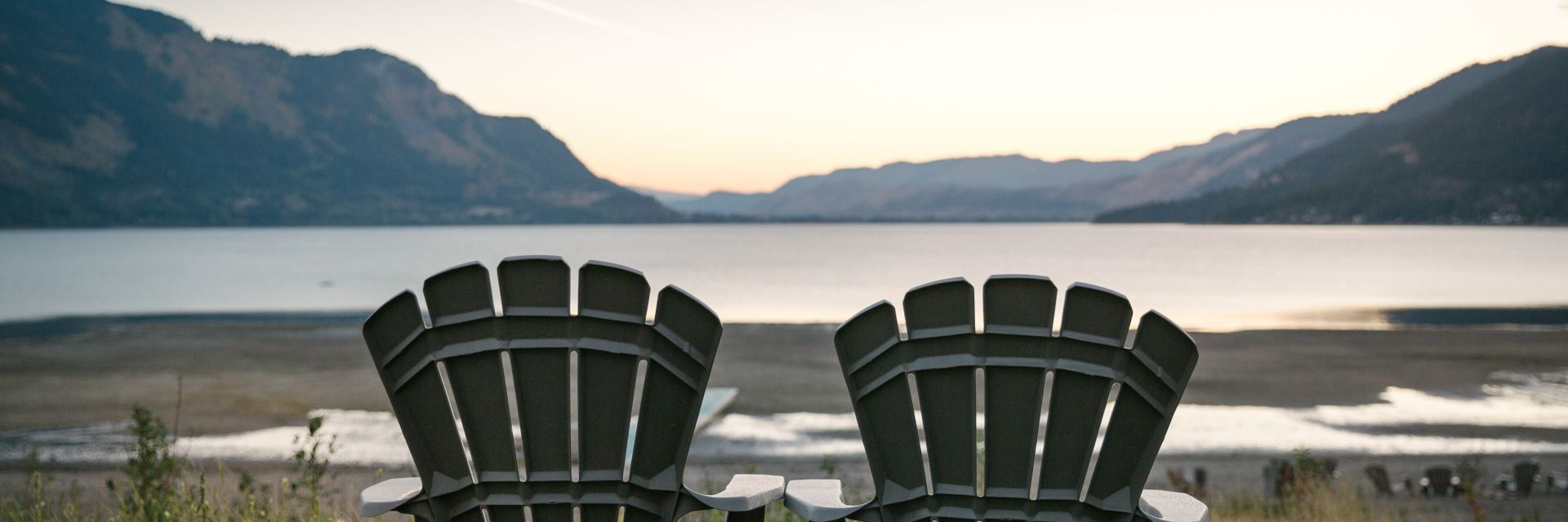 two beach chairs sit facing a body of water with mountains in the background