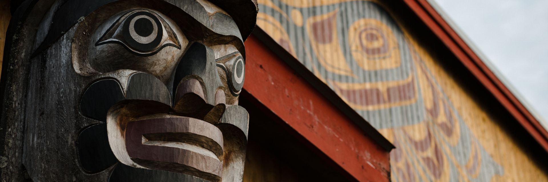 A closeup of a totem pole next to a yellow building