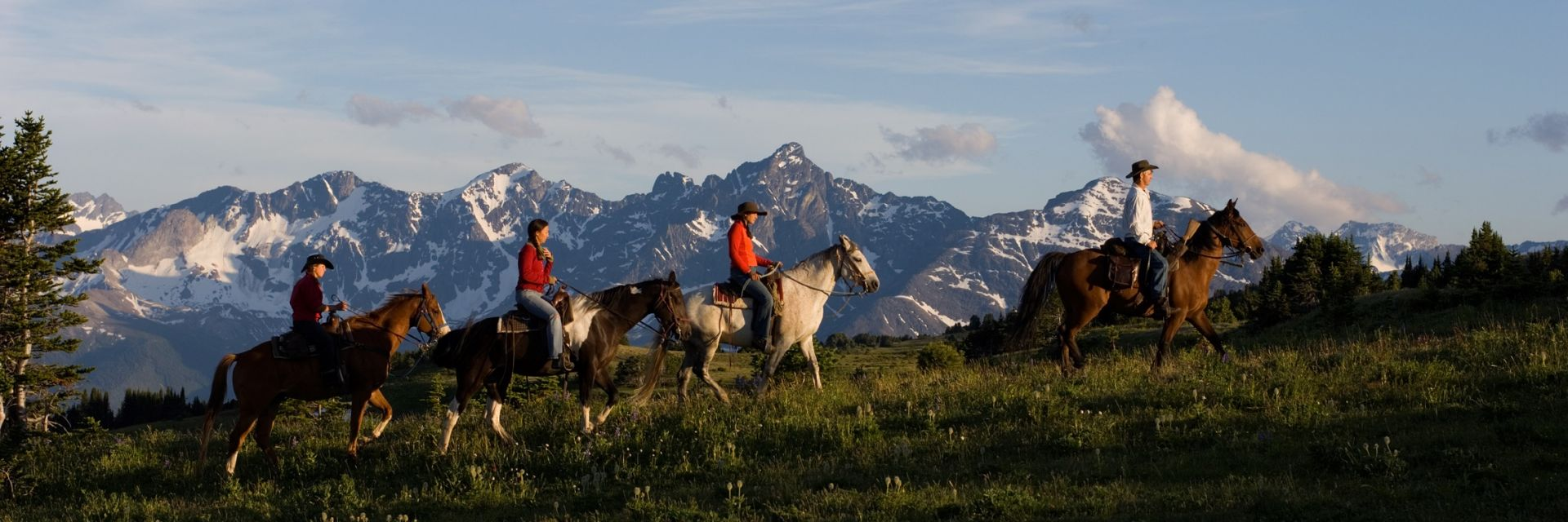 Four horses and riders make their way along a hill with the Potato Mountains in the background