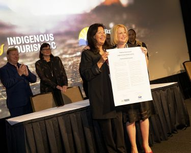 Two women hold the Indigenous Tourism Accord recently signed by ITBC and the Province of BC