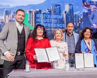 Members of ITBC and ITAC smile while holding a recently signed MOU