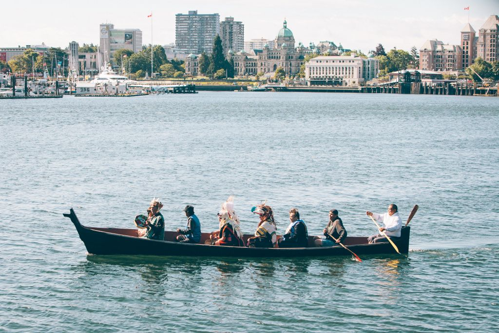 Seven people wearing traditional Indigenous clothing paddle a canoe in the Victoria harbour.