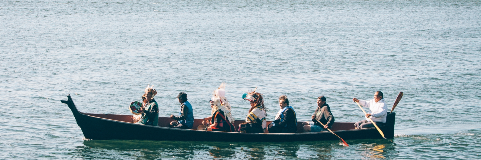 A group of people wearing traditional Indigenous clothing paddle on a canoe in the Victoria harbour.
