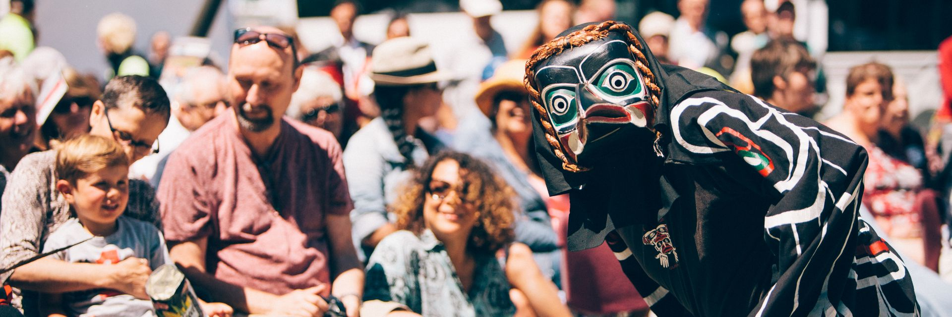 A dancer wearing a black mask and traditional Indigenous clothing performs for a crowd