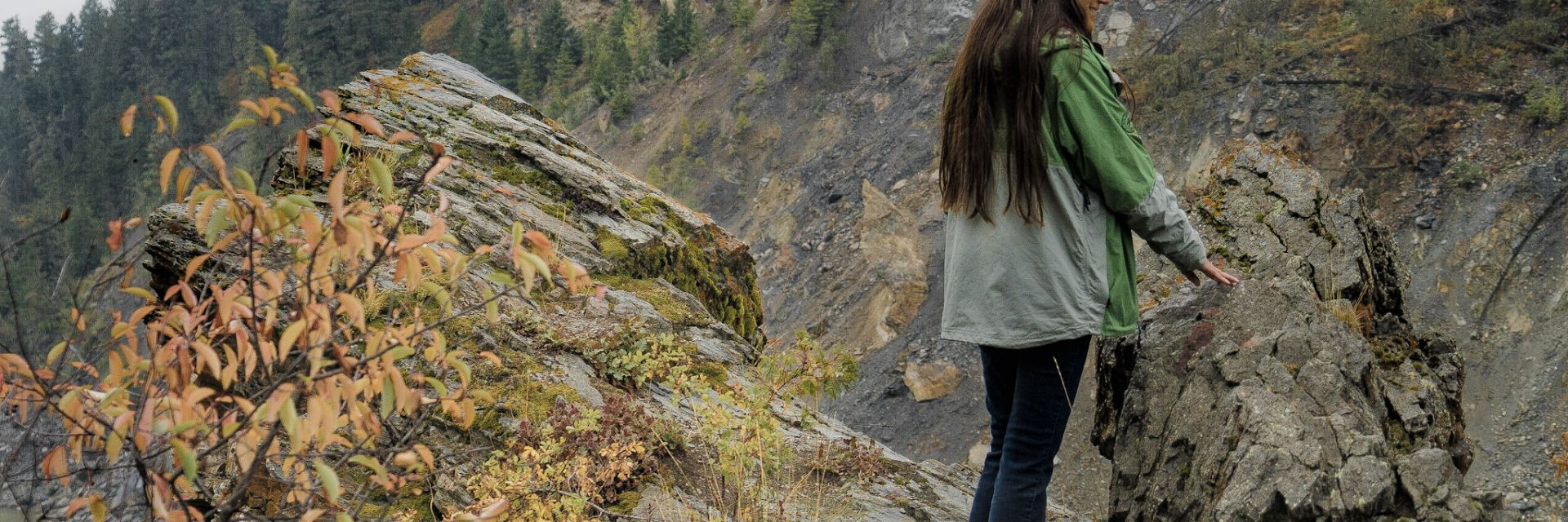 A woman steadies herself while standing at the edge of a cliff